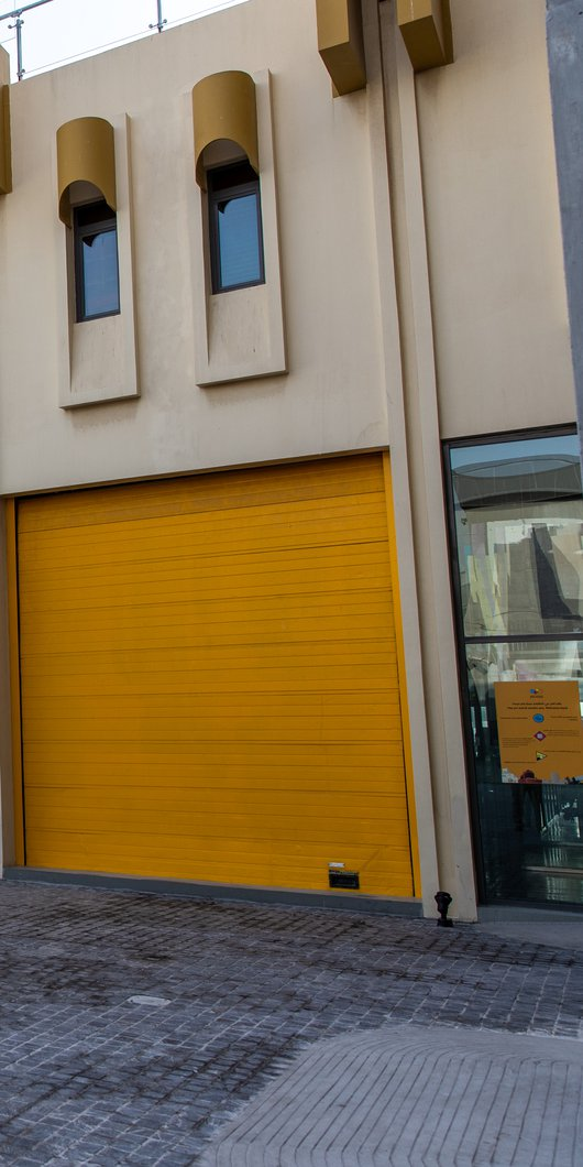 Landscape view of the exterior of the Fire Station's Garage Gallery's bright yellow door shutters