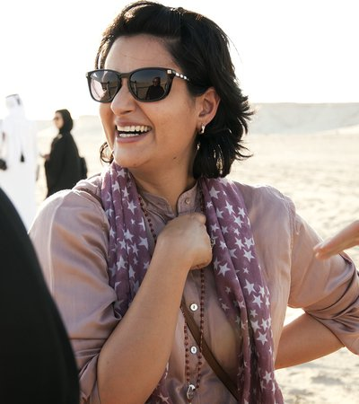 Portrait of Hala Mohammed Al Khalifa smiling and talking to people in a desert background