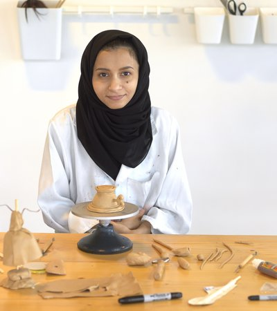 Hana Al Saadi sitting in a workshop surrounded by fresh clay objects