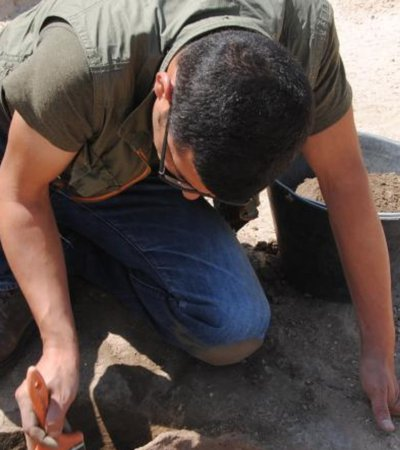 Hatem Arrok bending down and holding a brush while excavating fossils in a desert