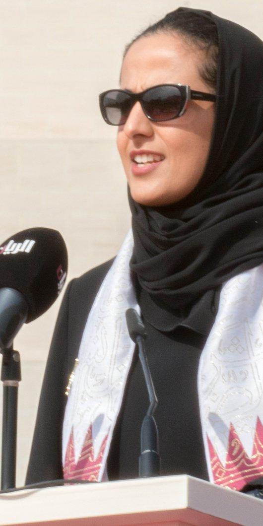 Her Excellency Shaikha Al Mayassa stands at a podium speaking