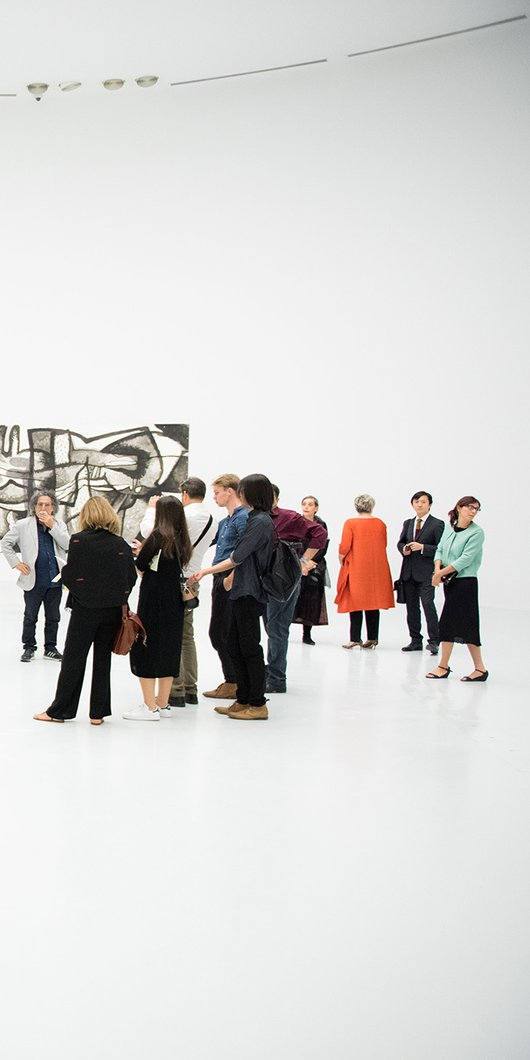 A group of visitors at the Al Riwaq's gallery space with works from Dia Al Azzawi's exhibition in the background
