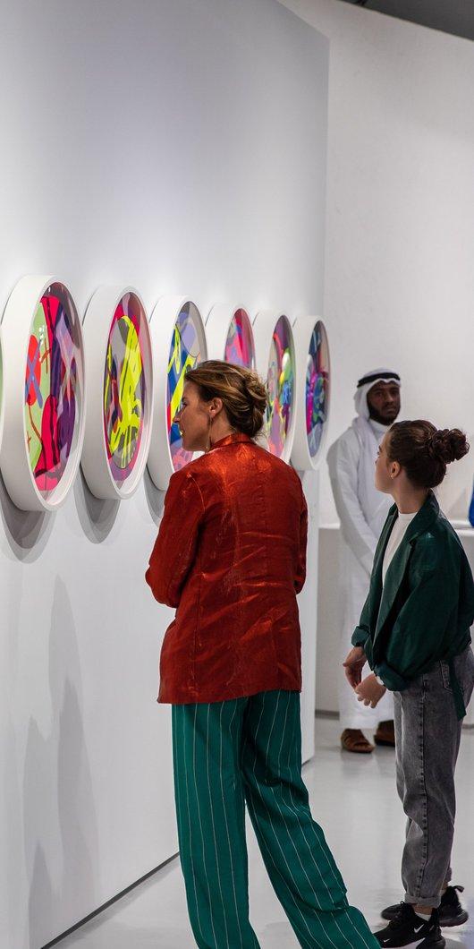 سيدتان تنظران إلى أحد الأعمال الفنية في معرض Kaws في كراج جاليري، مطافئ: مقر الفنانين