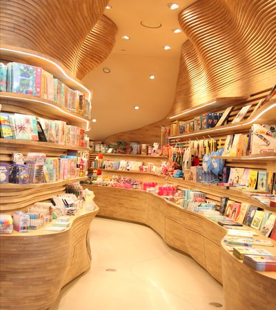 A view of the children's gift shop showing curving wooden shelves on two sides with books and art supplies displayed
