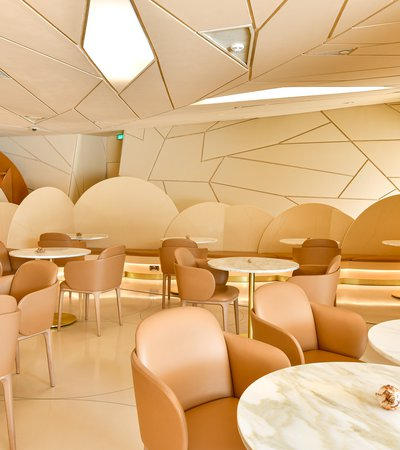 View of the interior of the Desert Rose cafe showing tables and chairs and the faceted shapes of the NMoQ building