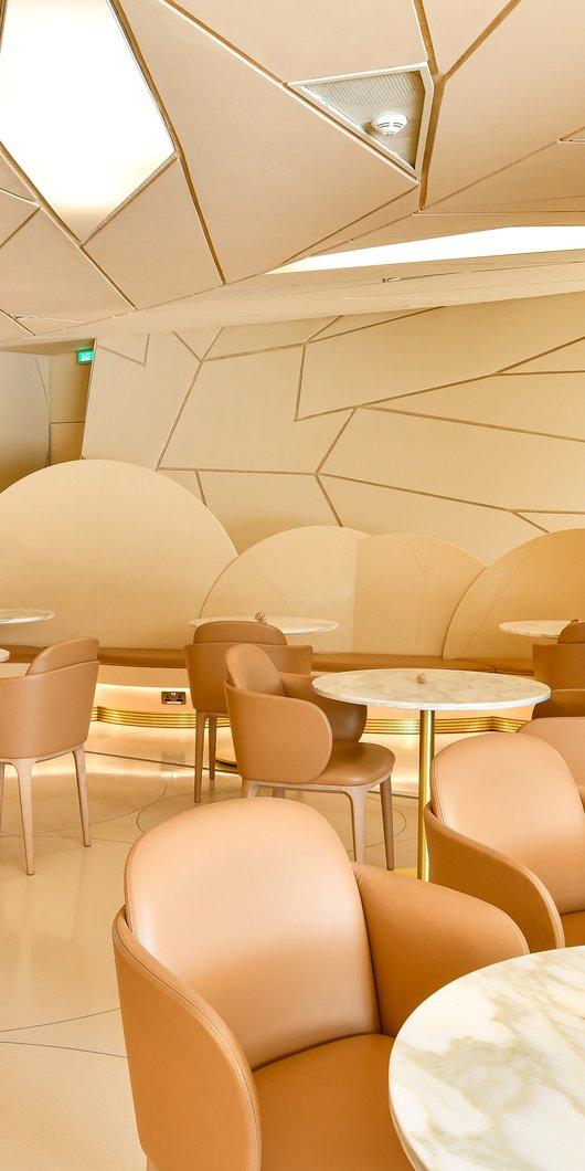 مشهد داخل مقهى وردة الصحراء يُظهر الطاولات والكراسي والأشكال متعددة الأوجه لمبنى متحف قطر الوطني