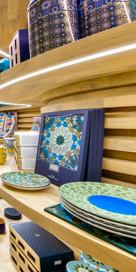 مشهد داخل متجر الهدايا في متحف قطر الوطني يُظهر المنتجات المحلية والمعروضة على الرفوف الخشبية المنحنية