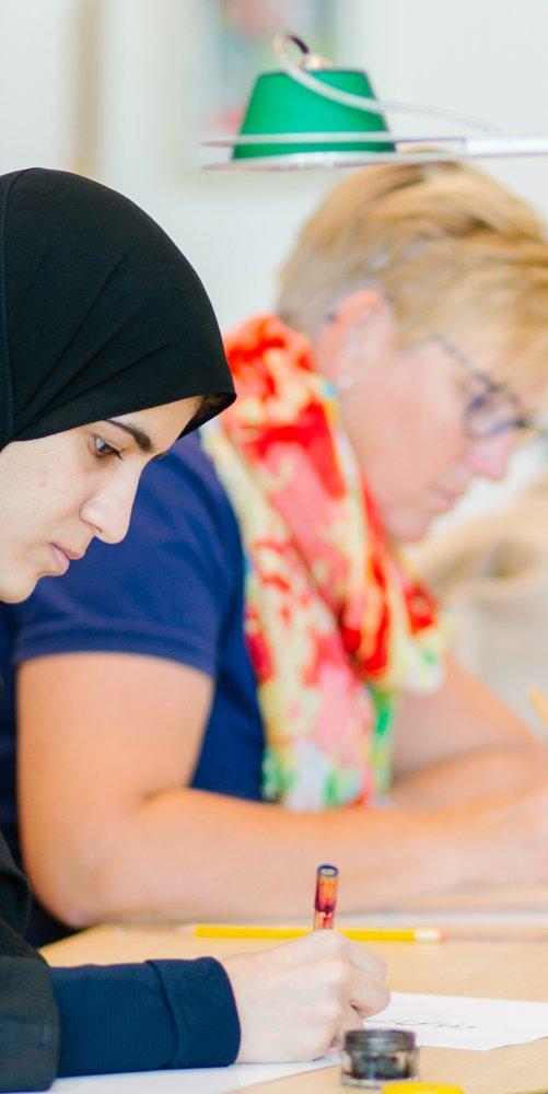 ثلاث نساء جالسات على مكتب يركزن على مهامهن