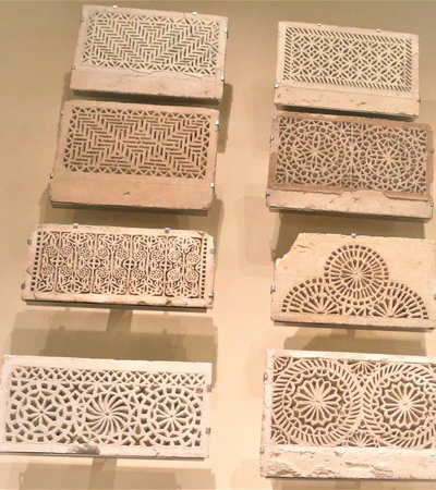 Several pieces of fawn-coloured ceramic pieces of intricately designed wall panels