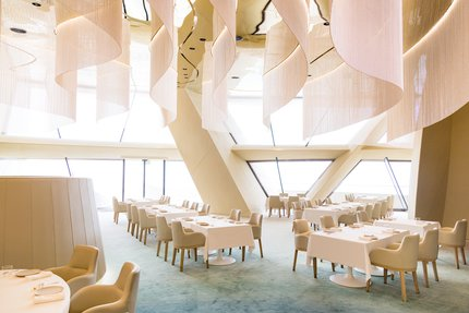 Interior view of Jiwan restaurant at National Museum of Qatar, showing table layout and interior architecture