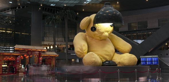 A sculpture of a large yellow teddy with a lamp above its head at Hamad International Airport