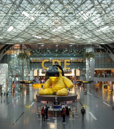 A sculpture of a  yellow teddy with a lamp above its head at Hamad International Airport