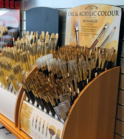 A shop display showing a range of different types and sizes of artist paint brushes