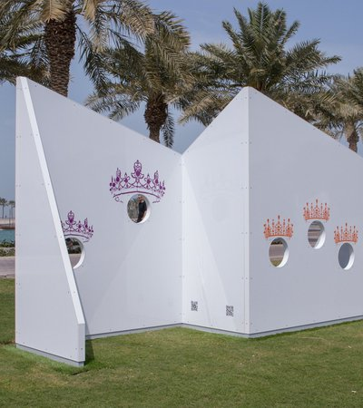 """White sculptures consisting of multiple unique """"head-in-the-hole"""" panels"""