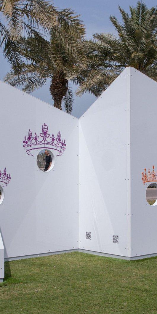 ألواح بيضاء ذات ثقوب مستوحاة من فكرة الرأس داخل الفجوة وتظهر أشجار النخيل في الخلفية