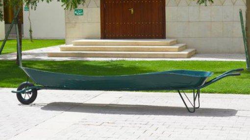 Long dark green wheelbarrow created by Hana Al Saadi standing in front of a small garden at Virginia Commonwealth University Qatar