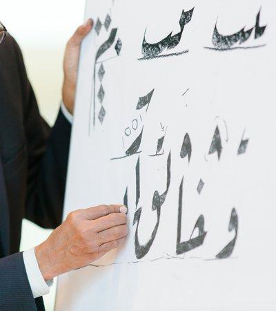 A man sketches Arabic calligraphy onto a white board