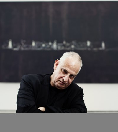 A portrait of Luc Tuymans framed by a black artwork in a museum while looking directly at the camera.