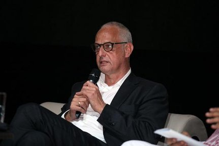 Luc Tuymans sitting on a couch while holding up a microphone to be interviewed.