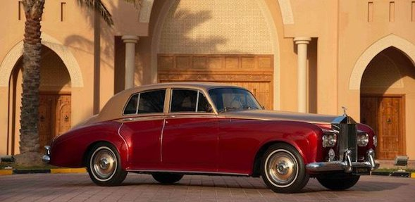 A shot of 1963 vintage Rolls Royce with a bright red sheen and gold details around the bumper and roof