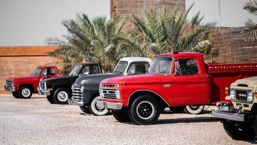 A row of classic cars parked in bright daylight for the Mal Lawal exhibition
