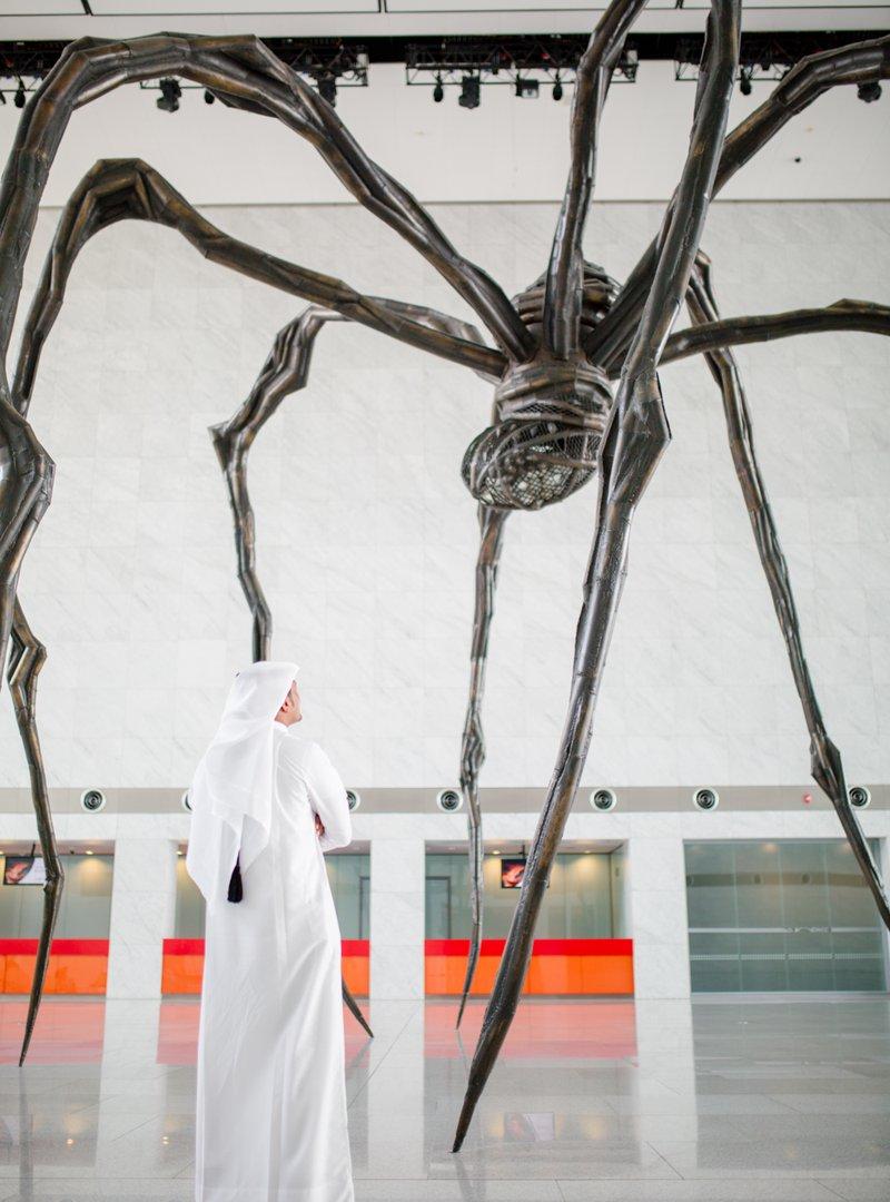 صورة لزائر يقف بجوار منحوتة ماما الضخمة في مركز قطر الوطني للمؤتمرات