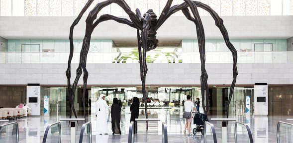 A wide-angle shot showing the full view of the spiders uniquely sculpted bronze and stainless steel legs