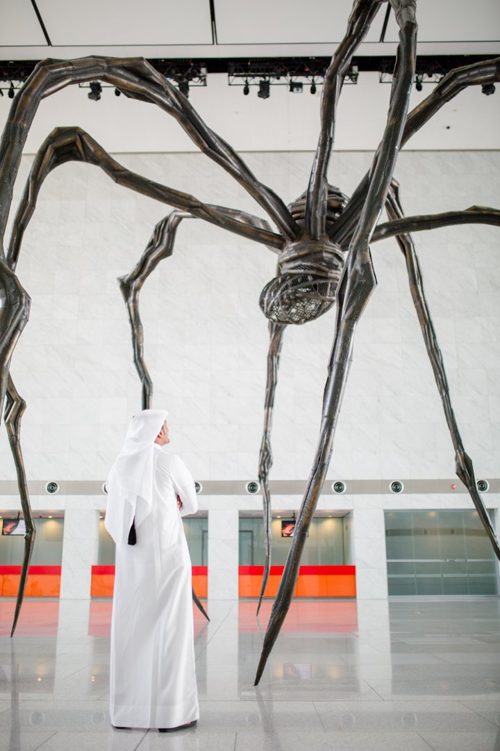 A portrait view of a visitor standing right next to the larger-than-life sculpture at QNCC