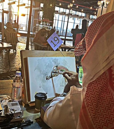 A man in traditional Qatari garb paints a colourful horse on canvas