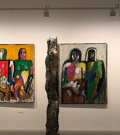 A shot of three paintings in the background with a sculpture placed in the middle of gallery space at Mathaf