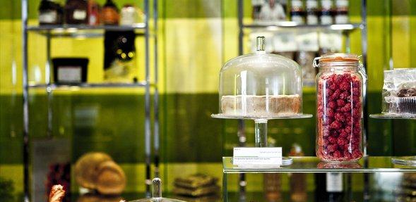 كعكة مستديرة معروضة في حافظة زجاجية، ومعروضات أخرى ملونة في مقهى متحف الفن الإسلامي
