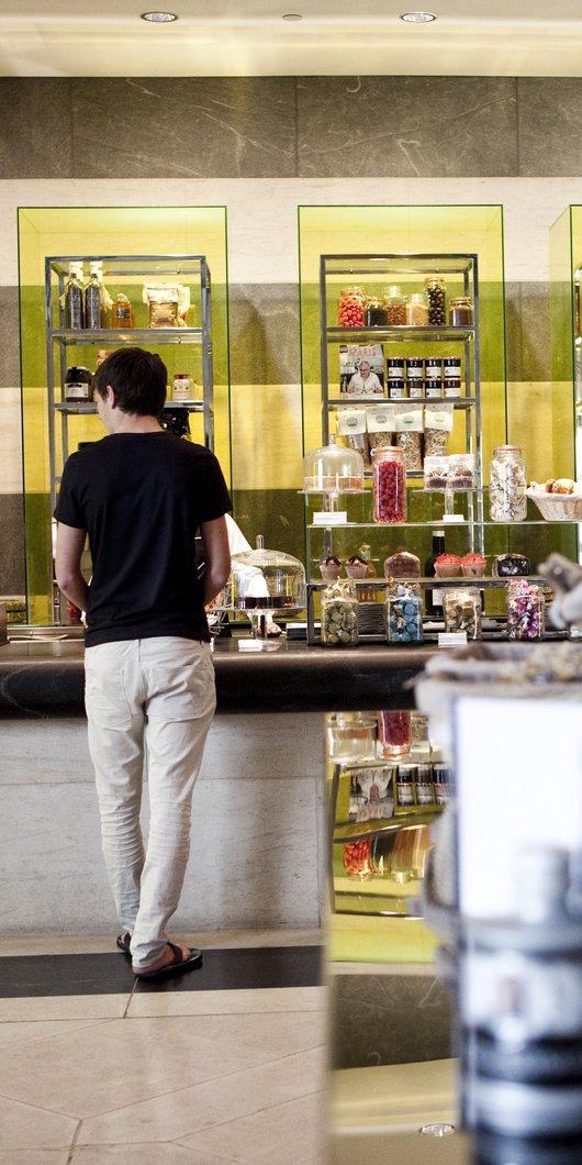 رجل يقف عند طاولة الخدمة في المطعم، حيث تظهر الأطعمة والمشروبات ملونة معروضة على طول الجدار الخلفي