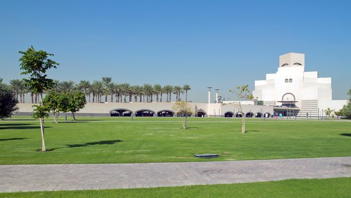 An open parkland space with green grass and native trees and the Museum of Islamic Art in the background