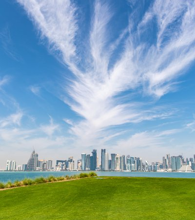 A panorama of Doha's skyline behind a large green grassy area
