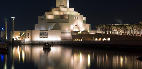 متحف الفن الإسلامي مضاء ليلاً بألوان ساطعة منعكسة على المياه المحيطة بالمبنى