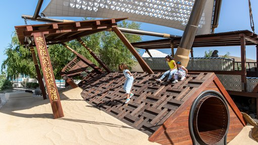 Three children having fun as they play on the wooden boats in the Nakilat Adventure Ship playground at NMoQ