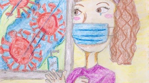امرأة ترتدي كمامة زرقاء وتقف أمام لوحة تظهر فيها رسومات لفيروسات بحجم كبير