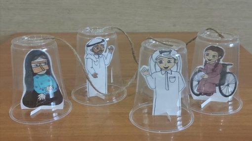 رسومات تمثل أربع شخصيات بالزي القطري التقليدي ملصقة على كؤوس بلاستيكية