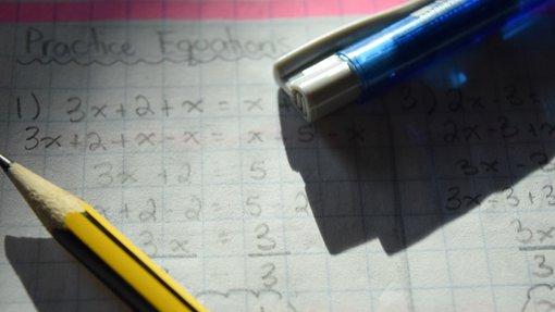 صورة قلمين على صفحة مكتوب عليها مسائل رياضية