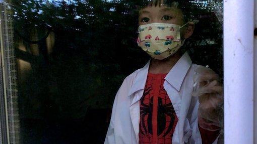 طفلة تنظر من خلف زجاج النافذة وترتدي زي سبايدرمان وفوقه ثوب الطبيب وكمامة على وجهها