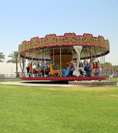 A brightly painted carousel with colourful animals for children to ride, in parkland with MIA in the background