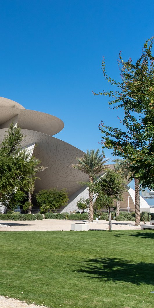 Landscaped gardens with green grass and native plants and trees surrounding the National Museum of Qatar