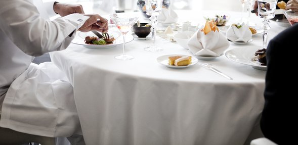 مشهد داخل مطعم إدام يعرض عدد من الأشخاص يجلسون على طاولة بيضاء ويأكلون غداءً منوعاً