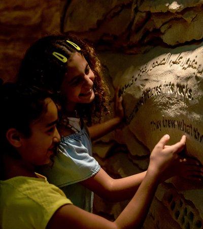Two smiling children exploring the wall carvings in NMoQ's Cave of Wonders