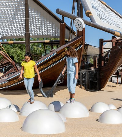 Two children in NMoQ's playground standing on top of round silver balls sunken into sand with two large wooden boats (dhows) in the background