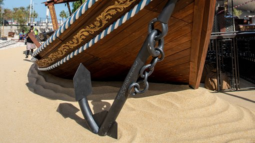 A view of the front of a large wooden boat (dhow) with a white sail, painted decorative sides and huge metal anchor standing on the sand