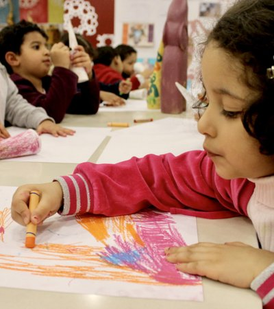 A group of children at a drawing workshop with scattered crayons and papers on the table