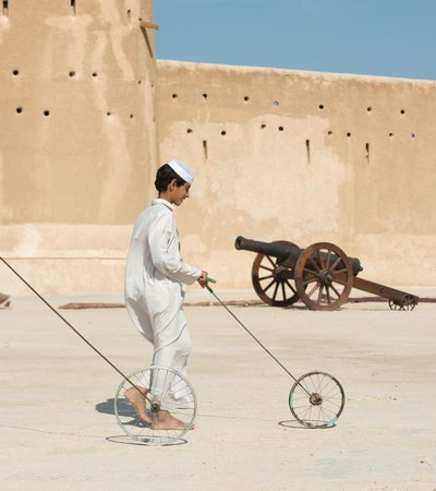 Two boys dressed in traditional Qatari attire hoop rolling with Al Zubarah fort in the background