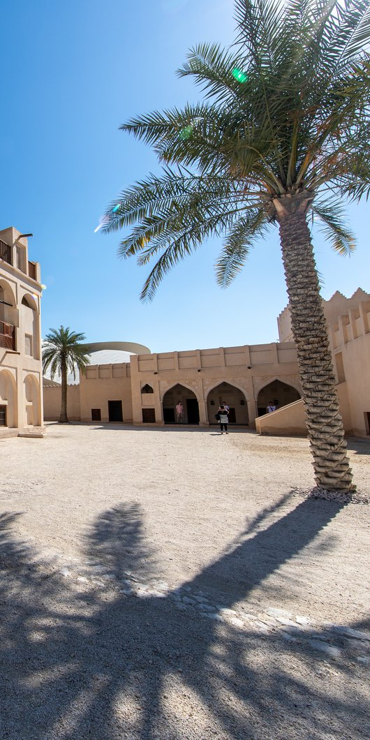 Restored historic palace with arches and sand coloured buildings in the background