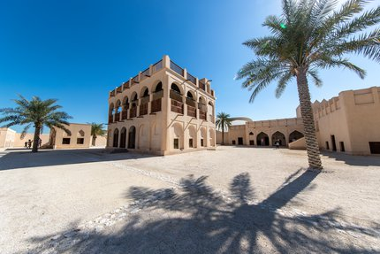 قصر تاريخي تمّ ترميمه بأقواس مميزة وتبدو بعض المباني بلون الرمل في الخلفية